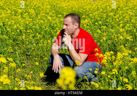 Man in a field of yellow flowers thinking of what tomorrow holds. - Stock Photo