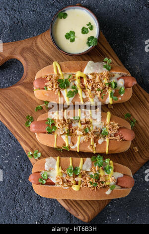 Hot dogs with sausage, fried onion, coriander leaves, cheese sauce and mustard, served on wooden serving board over - Stock Photo