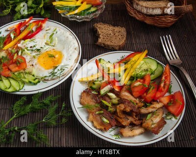 Fried bacon, eggs and vegetables with pepper, tomato and greens on white plates on a table on a bamboo napkin - Stock Photo