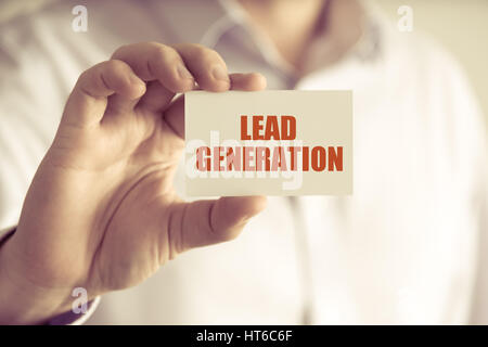 Closeup on businessman holding a card with text LEAD GENERATION, business concept image with soft focus background - Stock Photo