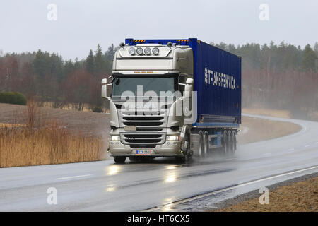 SALO, FINLAND - MARCH 3, 2017: Scania R450 semi truck of platinum color hauls cargo trailer along road in wet weather - Stock Photo