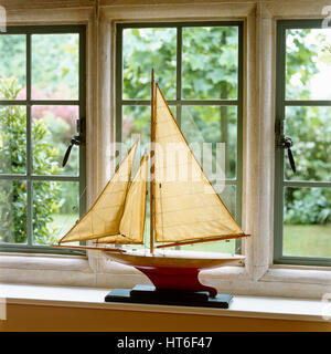 Model sailboat on windowsill. - Stock Photo