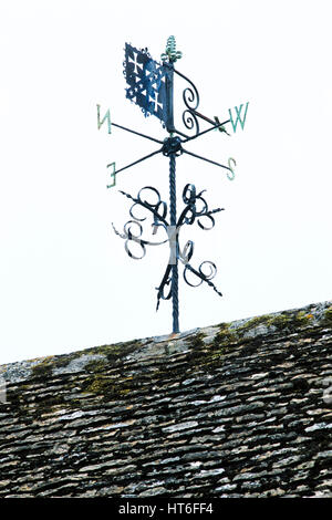Weather vane on tiled roof - Stock Photo