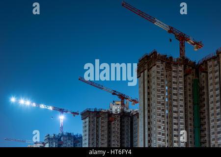 Three cranes and building at night - Stock Photo