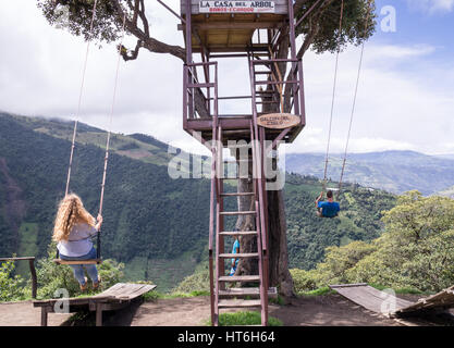 Banos, Ecuador on November 18, 2015: Tourists enjoying the giant swing at the treehouse Casa del Arbol in the Andes - Stock Photo