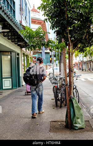 Honolulu, Hawaii - August 6, 2016: A man walks past bicycles in historic downtown Chinatown. - Stock Photo
