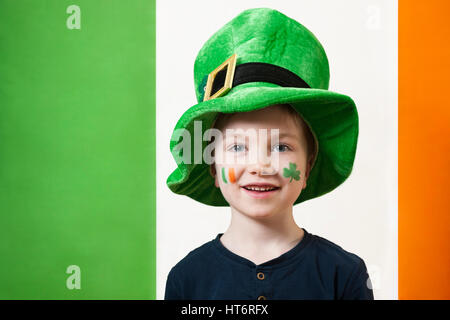 A cute smiling boy wearing a leprechaun hat and with a shamrock and Irish tricolour flag painted on his face for - Stock Photo