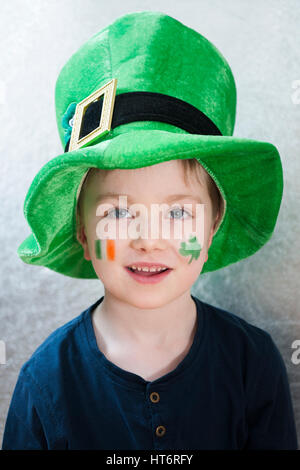 A cute smiling young boy wearing a leprechaun hat and with a face painted Irish tricolor flag and a shamrock for - Stock Photo