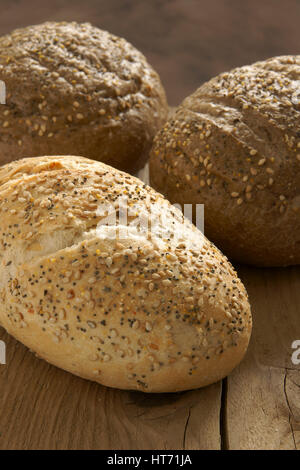 Rustic wholegrain loaves on a wooden bread board - Stock Photo