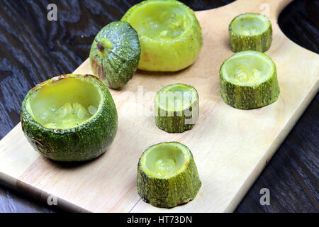 Emptied zucchini on wooden cutting board lying on a dark wooden table - Preparing stuffed zucchini recipe - Selective - Stock Photo