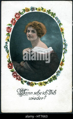 A postcard printed in Germany, shows a portrait of a beautiful woman. The inscription in German: When will I see - Stock Photo