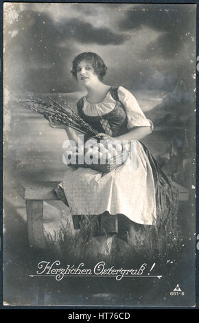 A postcard printed in Germany, shows a rural landscape, a girl with a basket of eggs and sprigs of willow. The inscription - Stock Photo