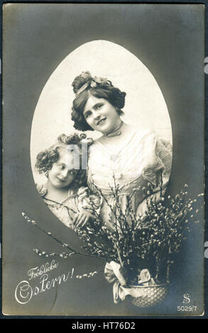 A postcard printed in Germany, shows a mother and daughter and a basket with willow branches. The inscription in - Stock Photo