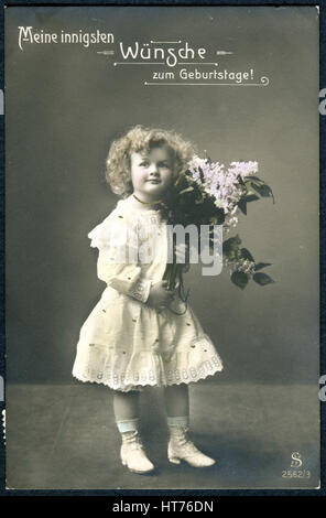 A greeting postcard printed in Switzerland, shows a girl with a bouquet of lilacs. The inscription in German: Happy - Stock Photo