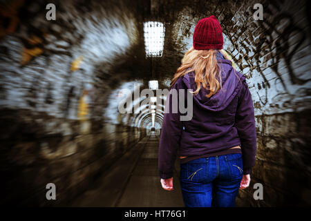 Young woman alone in a underpass - Stock Photo