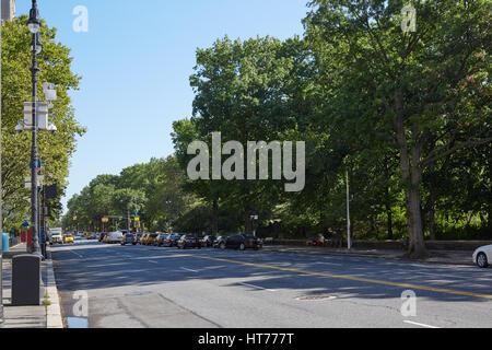 New York empty street near Central Park, green trees in a sunny day - Stock Photo