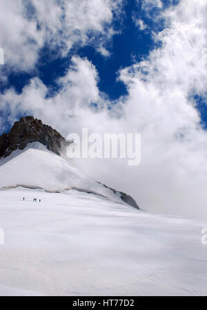 Giant Alps mountain summit as a sharp rock triangle covered in cracked icy snow and trails along the slope with - Stock Photo