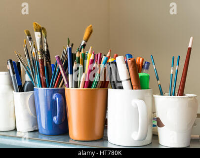 Close up of different used paint brushes, sharpened colored pencils, pens, and markers on colored mugs over blue - Stock Photo