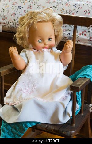 Close-up of child's plastic doll in miniature rocking chair next to bed in 1983 old house interior. - Stock Photo