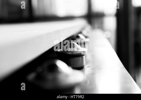 Black and White image of machinery rollers with product on top - Stock Photo