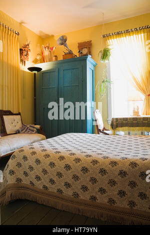 Master Bedroom With Floral Bedspread And Wooden Armoire In 1904 Victorian Old House Interior