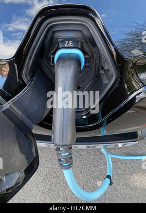 Electric car being recharged in street, London - Stock Photo