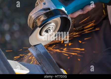 An angle grinder cutting through steel and giving off sparks - Stock Photo