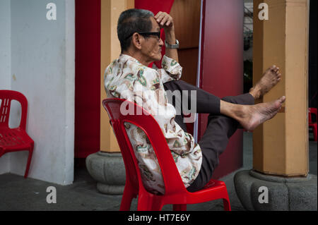 18.01.2017, Singapore, Republic of Singapore, Asia - A man relaxes on a plastic chair in Singapore's Chinatown district. - Stock Photo