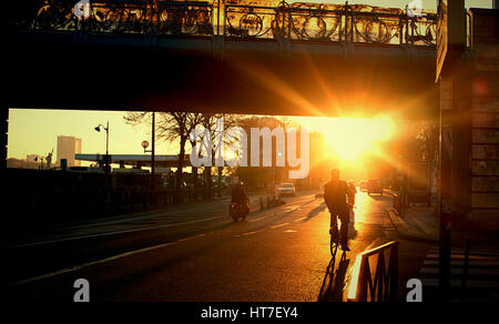 Man on a bike riding towards the sunset under a bridge in Paris, France - Stock Photo