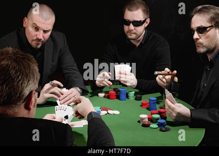 Photo of four men playing poker, smoking cigars and drinking whiskey. Focus is on the winning hand. - Stock Photo