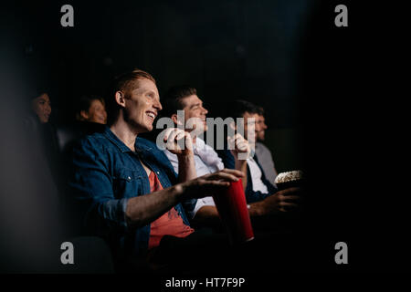 Smiling young man with friends in cinema hall watching movie. Group of people watching movie in theater. - Stock Photo
