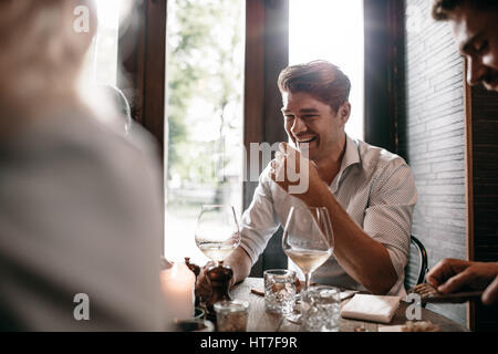 Indoor shot of young man smiling with friends at restaurant. Young people meeting at a cafe. - Stock Photo