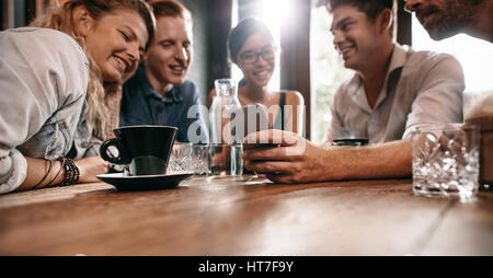 Horizontal shot of young friends watching photos on mobile phone. Group of young people sitting at cafe table and looking at smart phone.