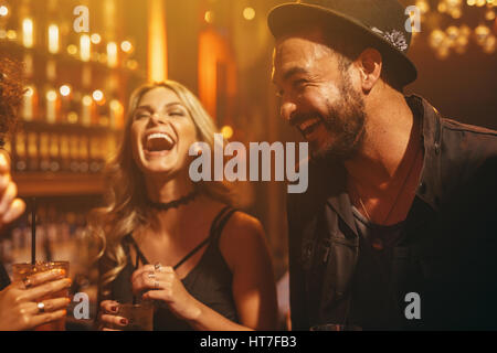 Group of people in the pub having fun. Young friends enjoying a night in club. - Stock Photo