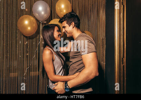 Shot of romantic young couple in the night club. Young couple having good times in the party at pub. - Stock Photo