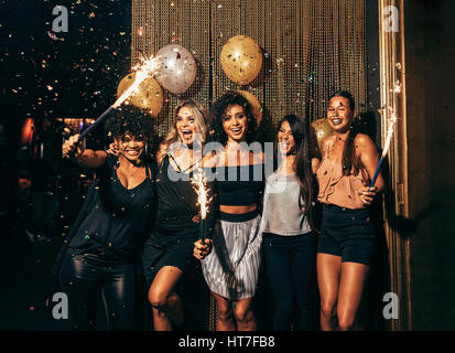 Shot of group of young women celebrating new years eve at the pub. Group of female friends with sparklers partying - Stock Photo