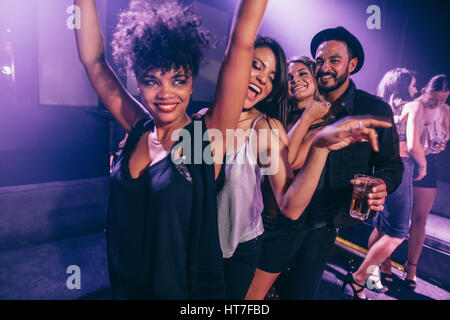 Group of friends dancing in night club. Young men and women having fun at disco club. - Stock Photo