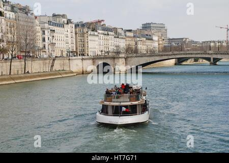 A pleasure boat cruises towards the Pont Saint Michel on the River Seine in Paris, France. Many sightseeing trips - Stock Photo