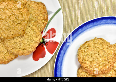 Homemade oat cookies on pretty plates - Stock Photo