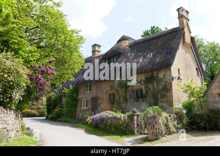 Thatched roof, stone cottage with flowering gardens,  by a country road, on a summer sunny day . - Stock Photo
