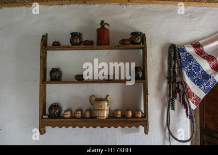 Craiova, Romania, November 8, 2009: Old traditional pottery on shelves  and a whip are seen in a house in the Museum - Stock Photo
