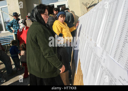 Sintesti, Ilfov county, Romania, November 22, 2009: Gypsy people check the electoral lists outside a polling station - Stock Photo