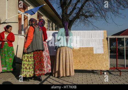 Sintesti, Ilfov county, Romania, November 22, 2009: Gypsy women check the electoral lists outside a polling station - Stock Photo