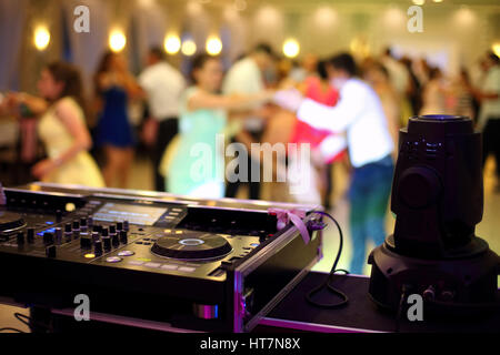 Dancing couples during party or wedding celebration by dj mixer - Stock Photo