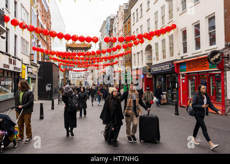 Tourists in Wardour street decorated with Chinese lanterns for the Chinese New Year celebrations. Chinatown, London, - Stock Photo