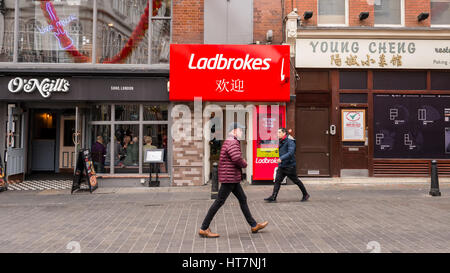 Ladbrokes betting agency store branch in Wardour street, Chinatown, London, UK with people walking and O'Neill's - Stock Photo