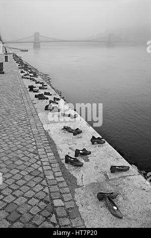 The 'Shoes on the Danube bank' memorial on the side of Pest, Budapest, Hungary. - Stock Photo