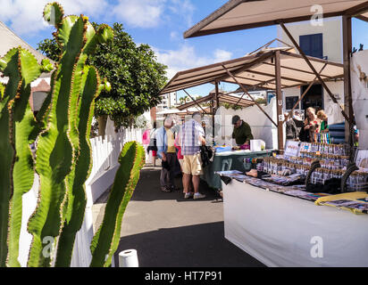 MARINA RUBICON LANZAROTE MARKET STALLS Sunday Market local artisan products & tourists with typical cacti in foreground - Stock Photo