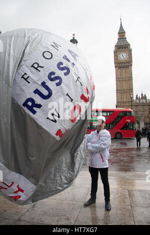 London, UK. 8th Mar, 2017. A group of men inflate a balloon with the inscription 'From Russia With Love Make Her - Stock Photo