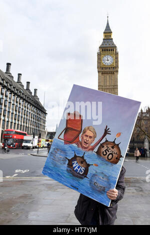 London, UK. 8th Mar, 2017. Satirical artist, Kaya Mar, is seen in Parliament Square carrying a topical painting - Stock Photo